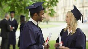 Estudiantes en vestido de la graduación con los diplomas que hablan, sacudiendo las manos y el abrazo almacen de video