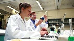 Estudiantes enfocados de la ciencia que examinan la sustancia química y que usan el ordenador portátil metrajes