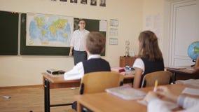 Estudiantes escuchar y contestar a las preguntas del profesor, colocándose en el mapa que cuelga en el tablero metrajes