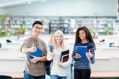 Estudiantes etchnic multi felices que se colocan en biblioteca de universidad Fotografía de archivo