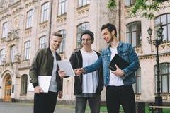 Estudiantes felices acertados que colocan el campus o la universidad cercano afuera Imagen de archivo libre de regalías