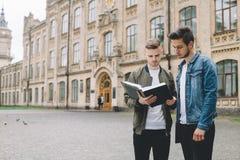 Estudiantes felices acertados que colocan el campus o la universidad cercano afuera Imagen de archivo
