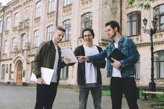 Estudiantes felices acertados que colocan el campus o la universidad cercano afuera Foto de archivo