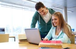 Estudiantes felices con el ordenador portátil en biblioteca Imágenes de archivo libres de regalías