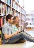 Estudiantes felices con el ordenador portátil en biblioteca Imagenes de archivo