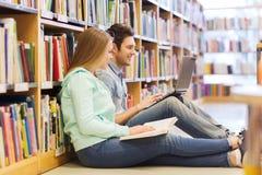 Estudiantes felices con el ordenador portátil en biblioteca Imagen de archivo