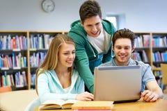 Estudiantes felices con el ordenador portátil en biblioteca Imagen de archivo libre de regalías