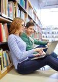 Estudiantes felices con el ordenador portátil en biblioteca Fotografía de archivo