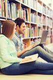 Estudiantes felices con el ordenador portátil en biblioteca Foto de archivo