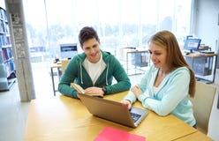 Estudiantes felices con el ordenador portátil y los libros en la biblioteca Fotografía de archivo
