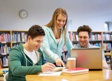 Estudiantes felices con el ordenador portátil y los libros en la biblioteca Foto de archivo