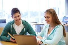 Estudiantes felices con el ordenador portátil y los libros en la biblioteca Imagenes de archivo