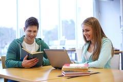 Estudiantes felices con el ordenador portátil y los libros en la biblioteca Imágenes de archivo libres de regalías
