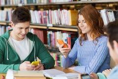 Estudiantes felices con los smartphones que mandan un SMS en biblioteca Fotografía de archivo libre de regalías