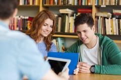 Estudiantes felices con PC de la tableta en biblioteca Imagenes de archivo