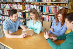 Estudiantes felices con PC de la tableta en biblioteca Fotos de archivo