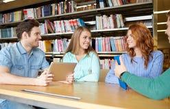 Estudiantes felices con PC de la tableta en biblioteca Imagen de archivo