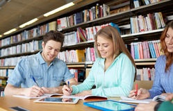 Estudiantes felices con PC de la tableta en biblioteca Imagen de archivo libre de regalías