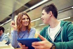 Estudiantes felices con PC de la tableta en biblioteca Imágenes de archivo libres de regalías