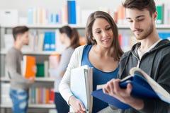 Estudiantes felices en la biblioteca Imagen de archivo libre de regalías