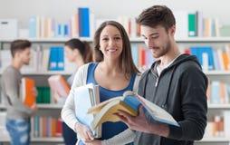 Estudiantes felices en la biblioteca Imagen de archivo
