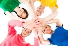 Estudiantes felices en la ropa colorida que se coloca juntas que lleva a cabo las manos Fotografía de archivo libre de regalías