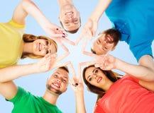 Estudiantes felices en la ropa colorida que se coloca junto de fabricación de sta Foto de archivo