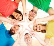 Estudiantes felices en la ropa colorida que se coloca junto de fabricación de sta Fotografía de archivo