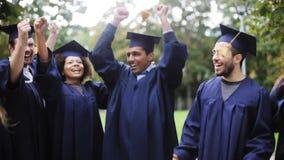 Estudiantes felices en tableros del mortero con los diplomas