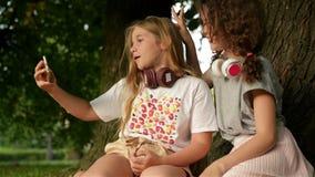 Estudiantes felices hermosos de las hermanas de las muchachas que se sientan en el aire libre del parque en hierba Están teniendo metrajes