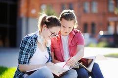Estudiantes felices jovenes con los libros y las notas al aire libre Fotos de archivo libres de regalías