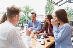 Estudiantes felices modernos que trabajan en el café junto en un fondo borroso Concepto activo de la forma de vida Foto de archivo
