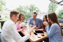 Estudiantes felices modernos que trabajan en el café junto en un fondo borroso Concepto activo de la forma de vida Fotos de archivo libres de regalías