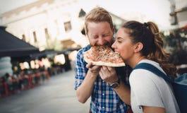 Estudiantes felices que comen la pizza en la calle Fotos de archivo libres de regalías