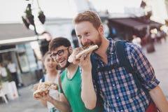 Estudiantes felices que comen la pizza en la calle Fotografía de archivo