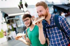 Estudiantes felices que comen la pizza en la calle Imagen de archivo libre de regalías