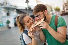 Estudiantes felices que comen la pizza en la calle Foto de archivo