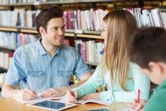 Estudiantes felices que escriben a los cuadernos en biblioteca Imagen de archivo