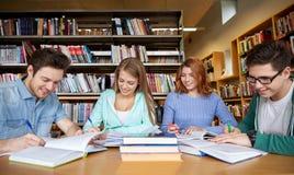 Estudiantes felices que escriben a los cuadernos en biblioteca Imagen de archivo libre de regalías