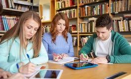Estudiantes felices que escriben a los cuadernos en biblioteca Fotografía de archivo