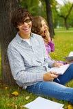 Estudiantes felices que estudian en parque del otoño Foto de archivo libre de regalías