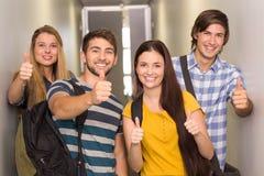 Estudiantes felices que gesticulan los pulgares para arriba en el pasillo de la universidad Imagen de archivo libre de regalías