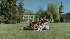 Estudiantes felices que miran el vídeo divertido en el teléfono elegante almacen de video