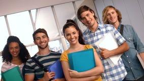 Estudiantes felices que miran la cámara con los pulgares para arriba la universidad metrajes