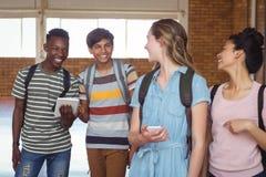 Estudiantes felices que obran recíprocamente mientras que usa el teléfono móvil y la tableta digital en campus Foto de archivo