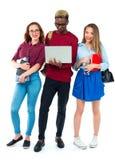 Estudiantes felices que se colocan y que sonríen con los libros, el ordenador portátil y los bolsos Imagen de archivo