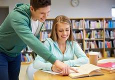 Estudiantes felices que se preparan al examen en biblioteca escolar Fotos de archivo
