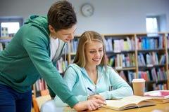 Estudiantes felices que se preparan a los exámenes en biblioteca Imágenes de archivo libres de regalías