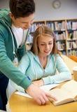 Estudiantes felices que se preparan a los exámenes en biblioteca Foto de archivo libre de regalías