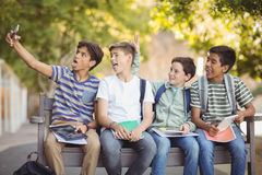 Estudiantes felices que se sientan en banco y que toman el selfie en el teléfono móvil Fotos de archivo libres de regalías